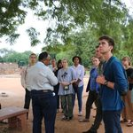 Students listen to a lecture while on a site visit.