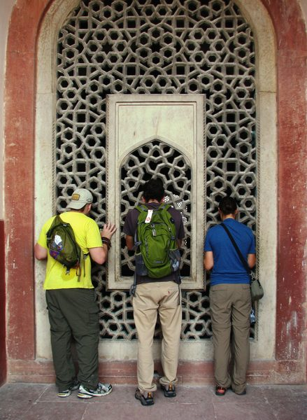 Three students peer into the window at Hamayun's Tomb in India