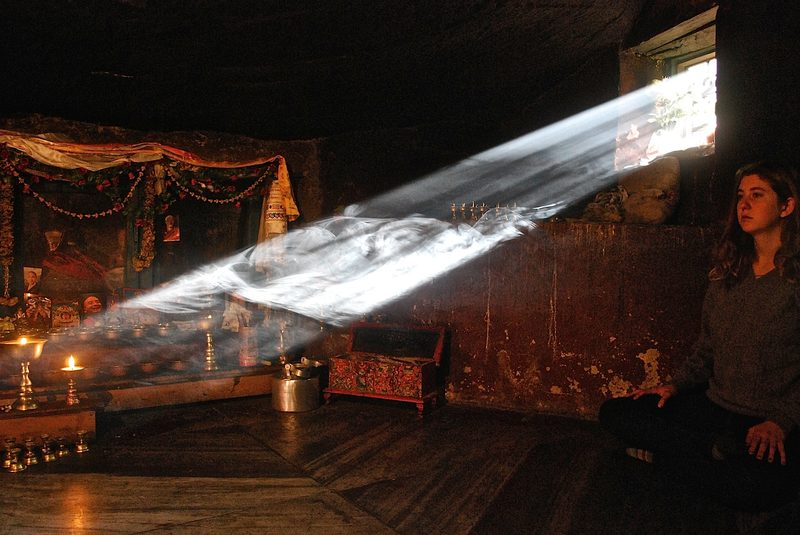 A student meditations in a dark room illuminated by a single shaft of light