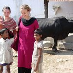 Students pose with children and a cow
