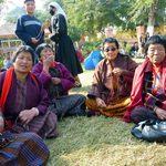 A group of women sit on the ground