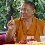 A monk lifts his finger in the air as if to make a point