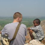 A student talks to a young boy on a mountaintop