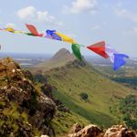 A man waves a string of bright cloth fabric in the wind on a mountain peak