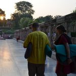 Students carry their meditation mats as the sun sets