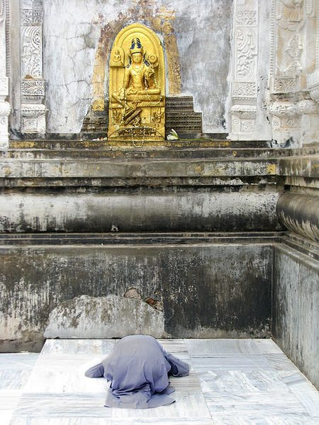Someone prays in front of a golden statue