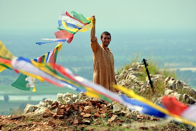 A man smiles while lifting a clothesline of bright cloth pieces