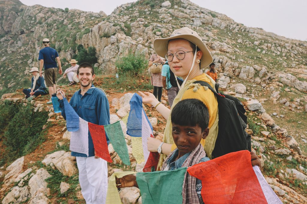 Students hold flags on a mountain top