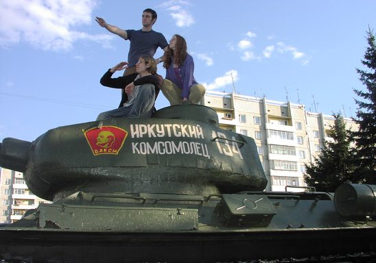 Three Students on the 2005 Carleton Moscow Program climb on top of an old Soviet tank in Siberia.