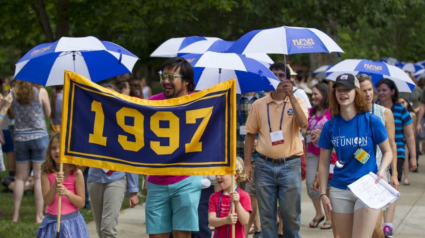 parade of people walking with umbrellas. People in the front are holding a class of 1997 banner