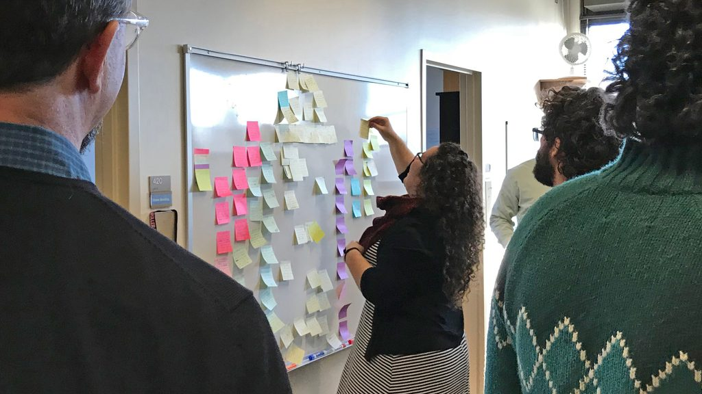 A woman adds sticky notes to a whiteboard while several men observe