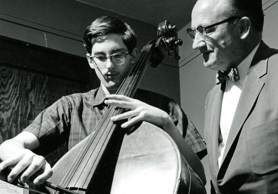A student receives bass lessons from instructor Kenneth Davenport at the music hall in 1964.