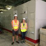 Two summer student interns standing in front of the new heat pump.