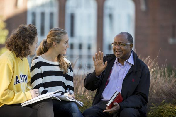 Professor talking to two students outside