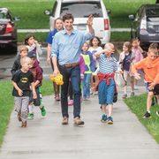 Professor Dan Groll walks on a sidewalk with a group of small children
