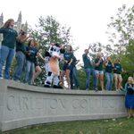 Students dancing on Carleton sign