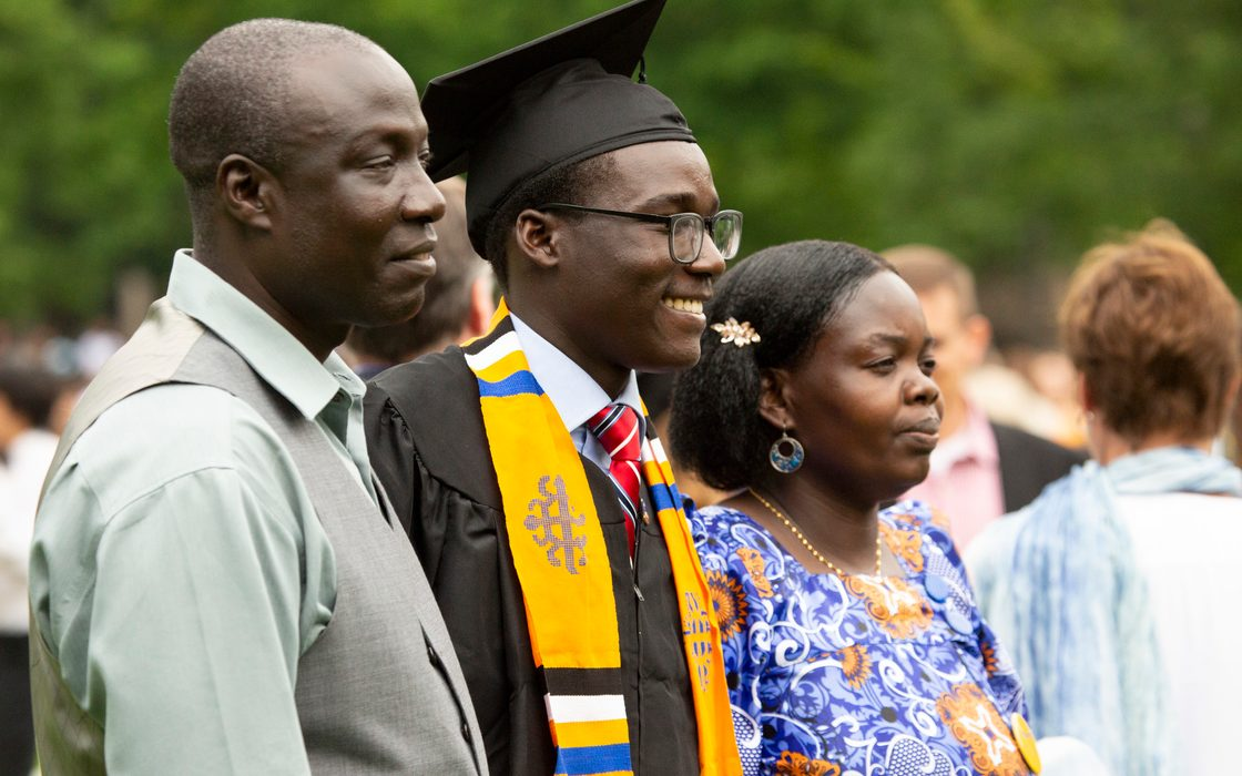 A graduate and his parents at commencement