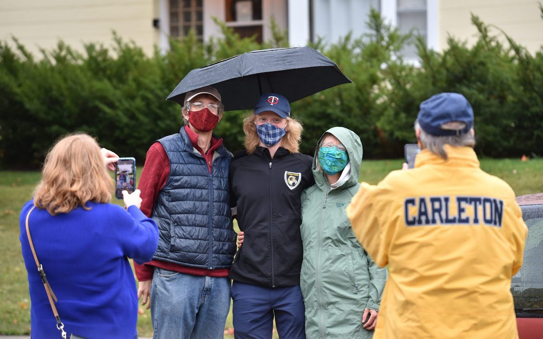 Masked student and parents pose for a photo