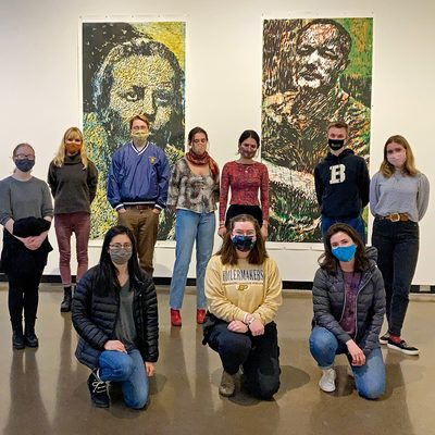 A group of students in an art gallery, wearing COVID masks