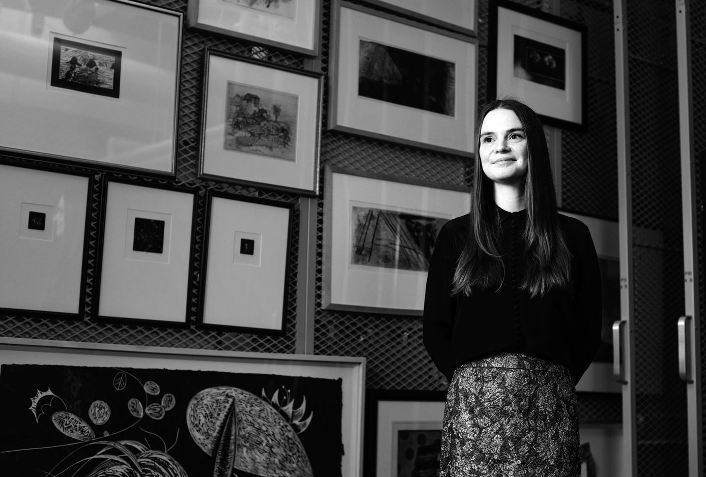 A woman with long hair stands in front of a wall of framed prints