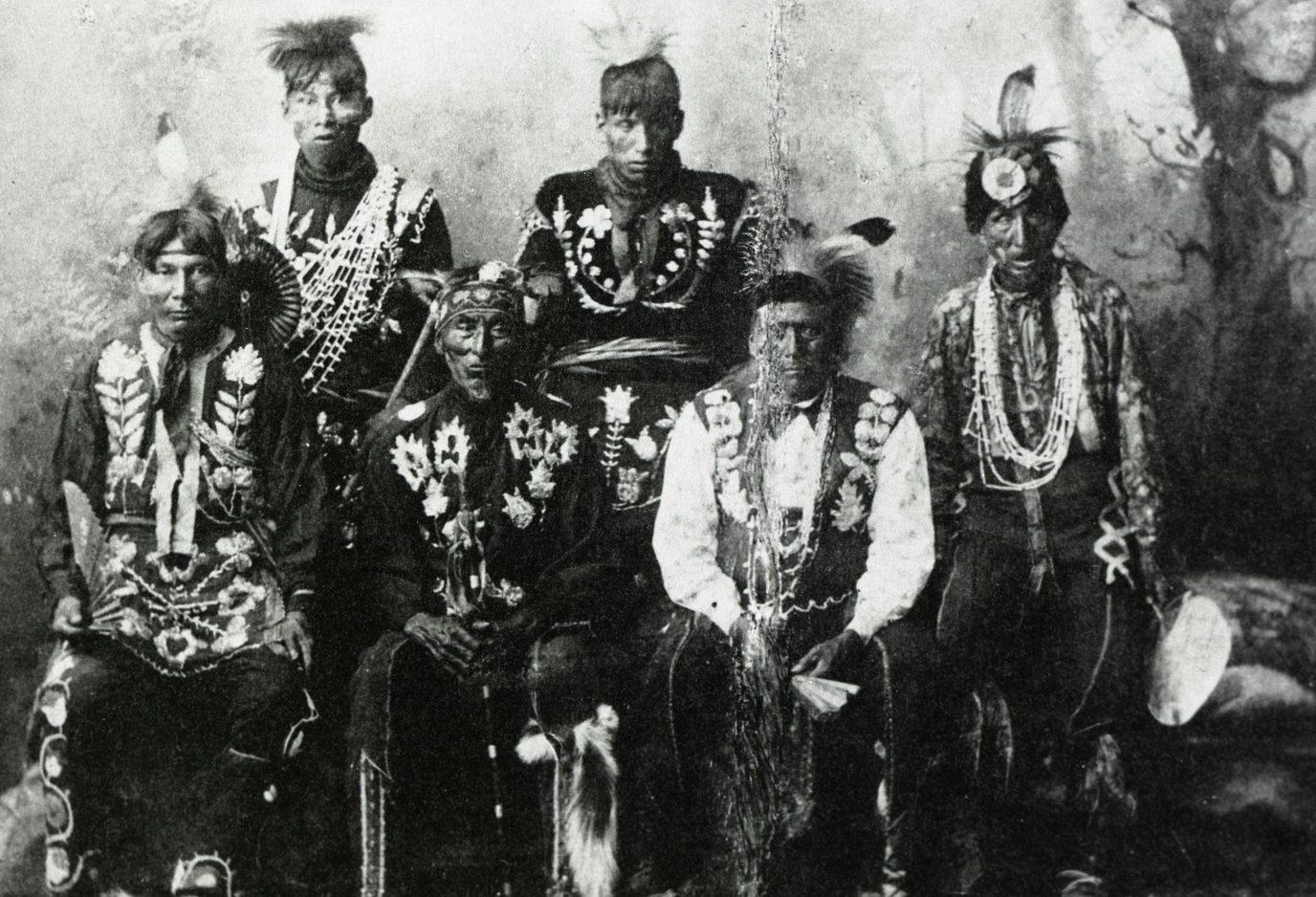 Historic black & white portrait of six Native American men in ceremonial attire