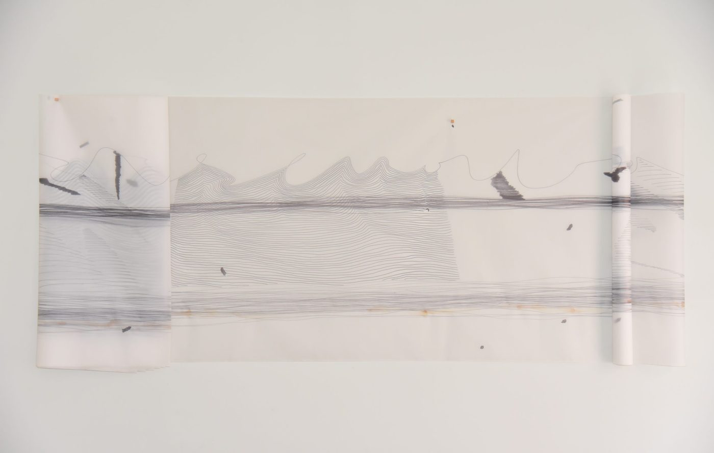 A piece of paper that is folded and tacked up onto the wall. On the paper there appears to be a landscape rendered in ink and drawn over with wavy lines. On the far right the waves are not filled in, and at the bottom there are streaks of coffee