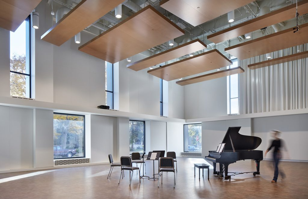 Image of Shackel Hall, a Music Dept. rehearsal space, with a piano, music stands, and chairs.
