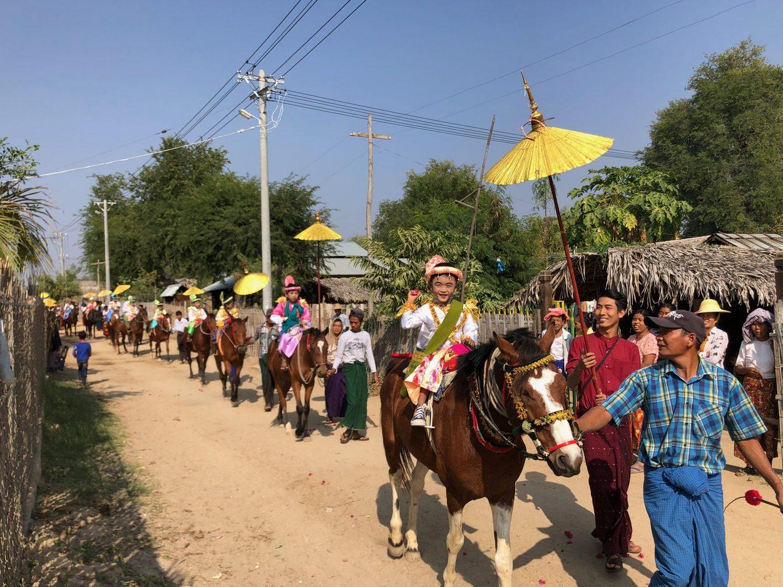 A young boy rides a horse in a village parade