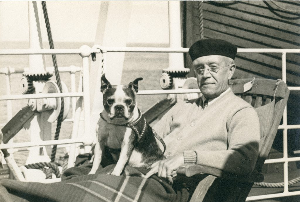 Beret-wearing Blayney on ship with dog