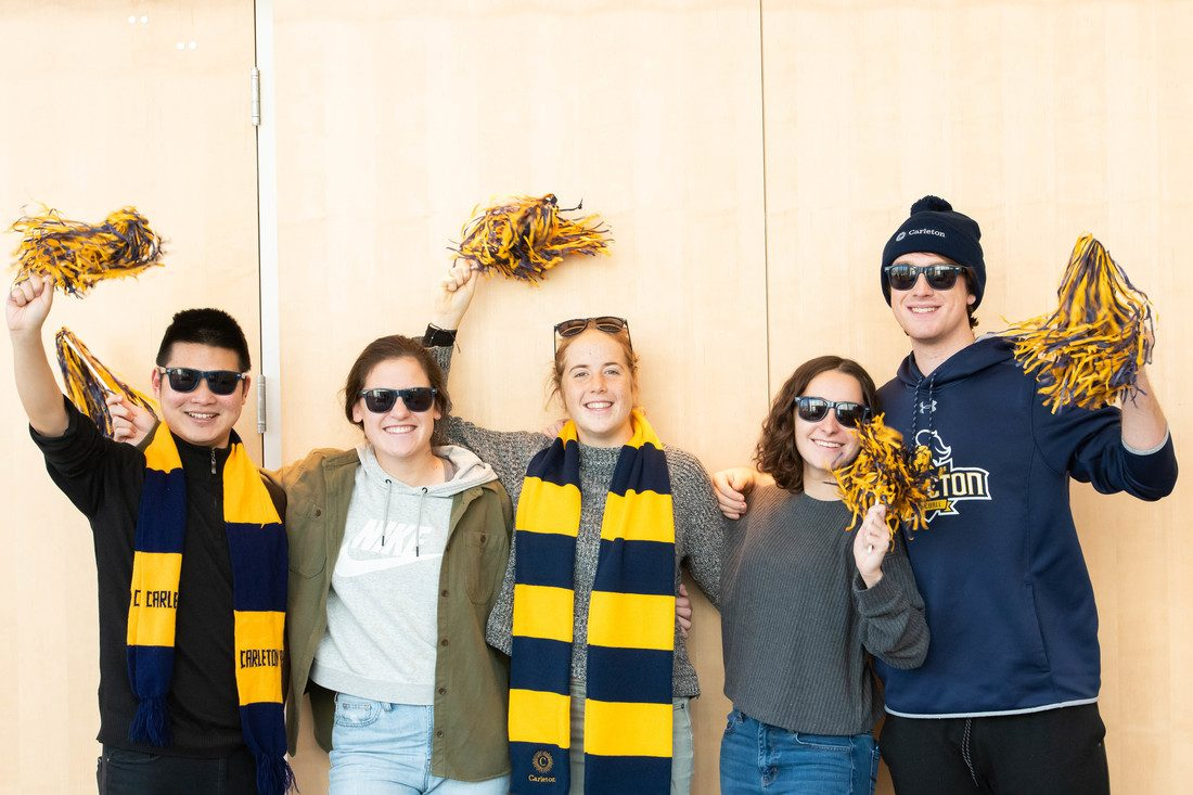 Students pose for a photo wearing Carleton gear