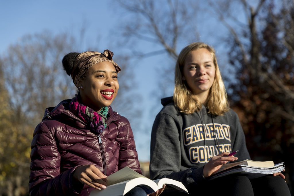 Two students read books outside on campus