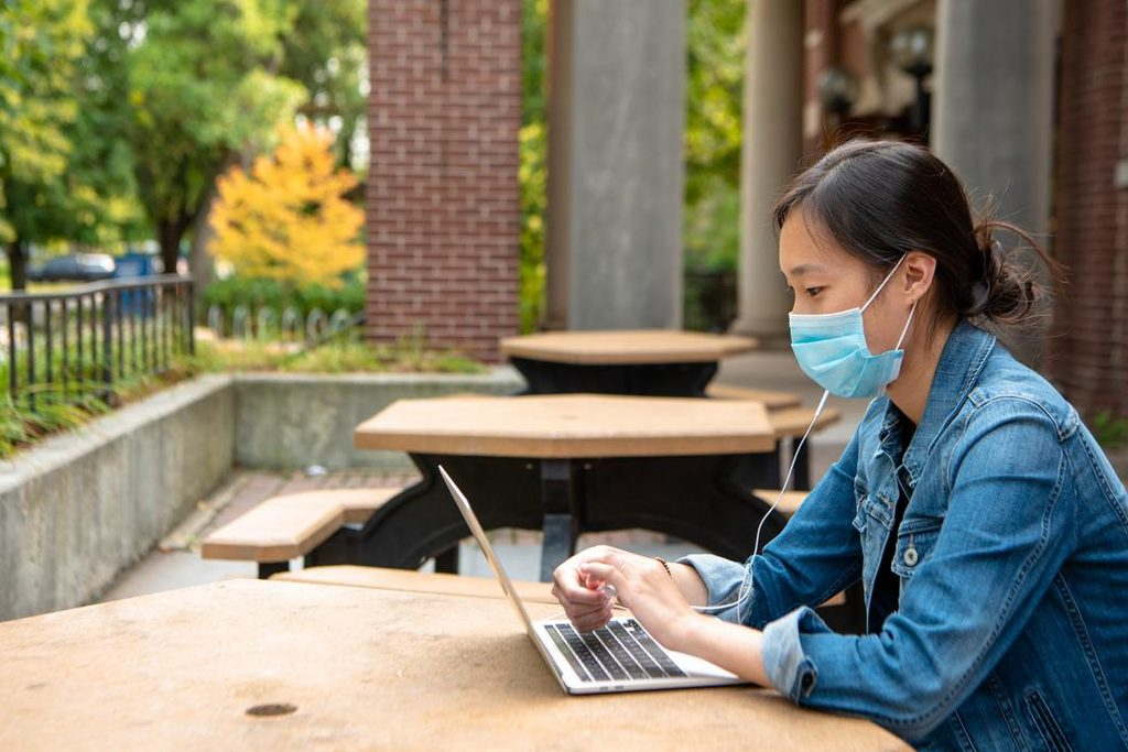 A student wearing a mask and using a laptop at an outdoor table