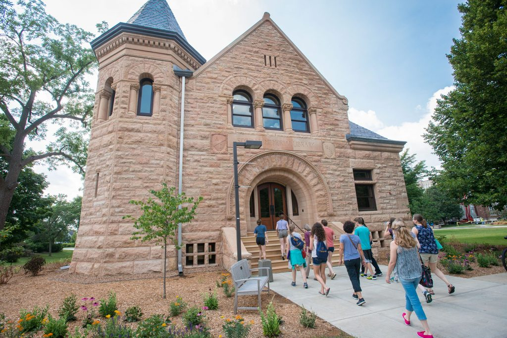 A group of prospective students walk past Scoville hall on a campus tour
