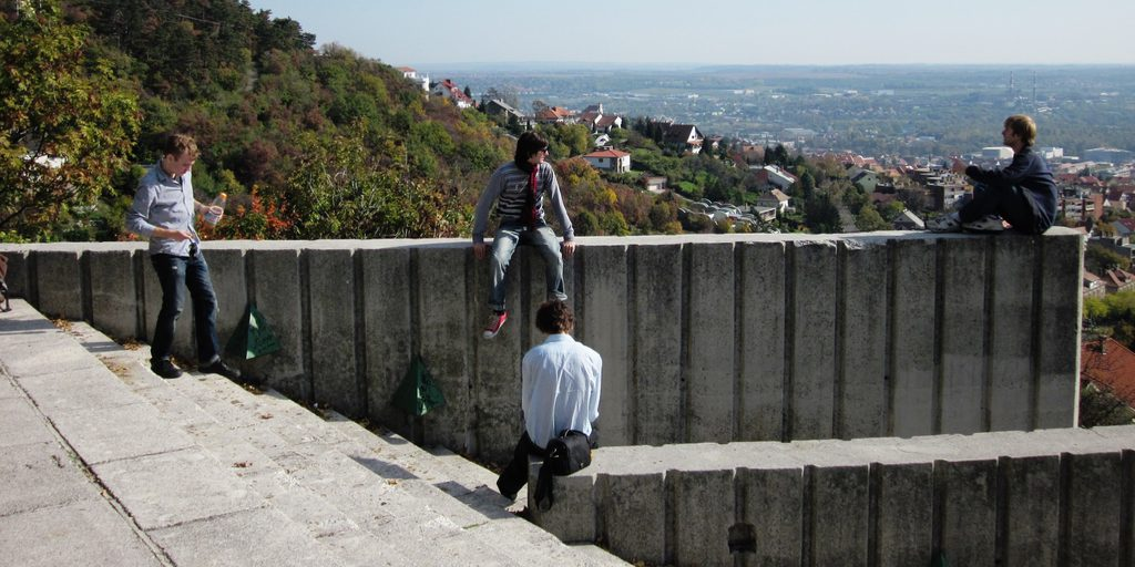 Four young men sit on a mountainside concrete wall