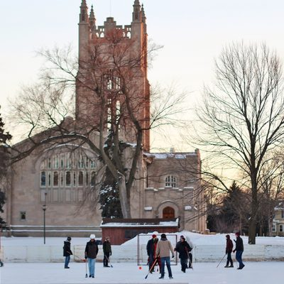 A broomball game on the bald spot ice rink, with Skinner Chapel in the background