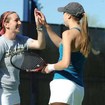 Two students high-five on a tennis court
