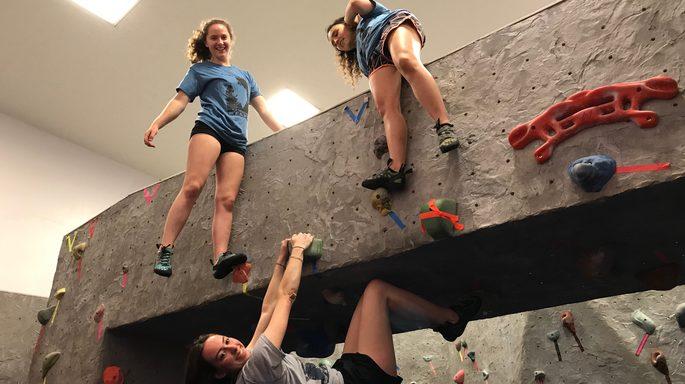 Three students climb a bouldering wall