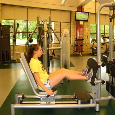 A student uses the seated leg press in the Fitness Center