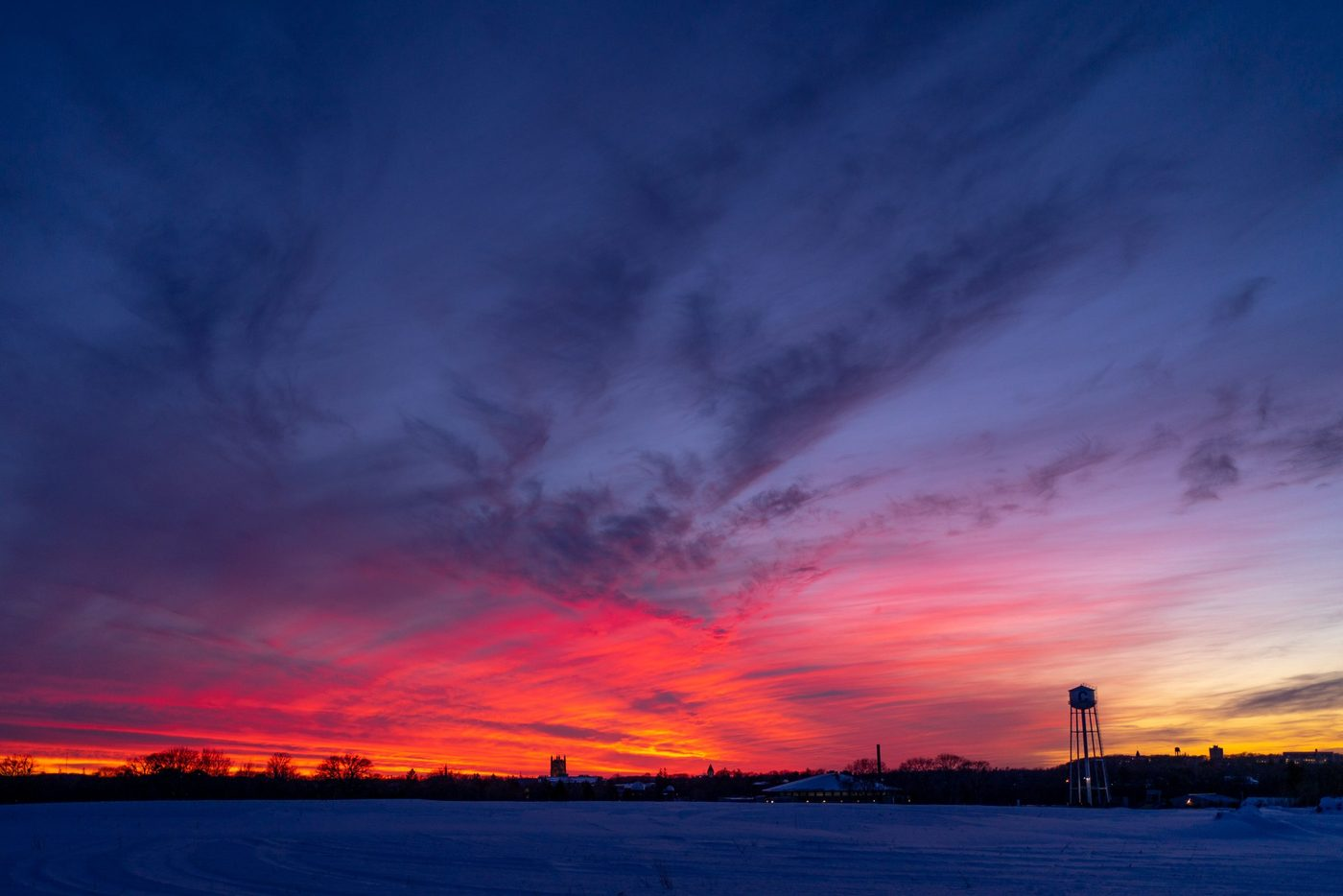 Colorful winter sunset overlooking a field with the Carleton water town and Skinner chapel peaking in the distance