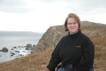 Professor Deborah Gross dressed in black outdoor apparel on the banks of several cliffs