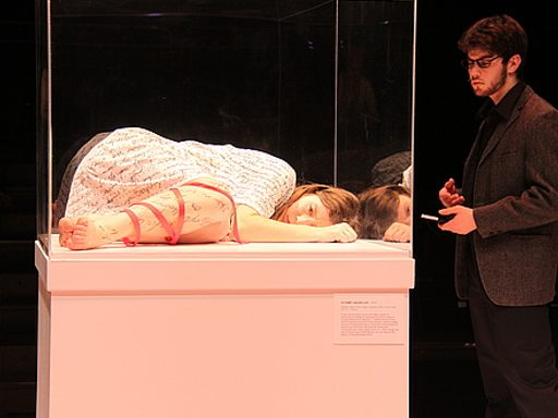 A woman laying in a museum display case, and a man looking at her