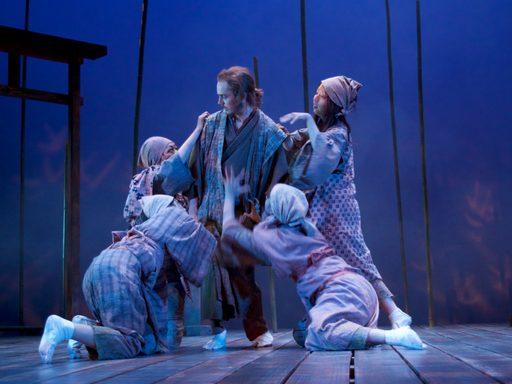 Four women reaching towards a standing man
