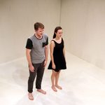 Man and a woman standing barefoot in a white room
