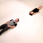 A man and a woman laying on a white floor with their feet on opposite walls