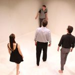 Man being cornered in an empty white room by three other actors
