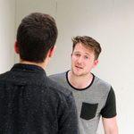 Two men in grey shirts talking