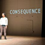 "Girl standing on stage and the word ""consequence"" projected behind her"