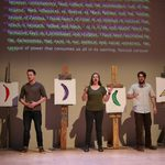 Actors standing next to paintings of colored bananas with words projected behind them