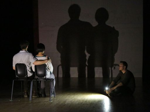 A seated couple and their silhouette projected on the back of the stage
