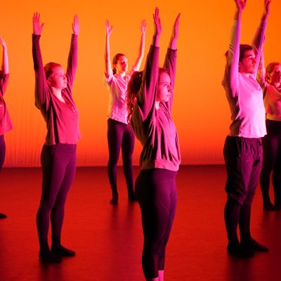Dancers stand onstage in red-orange light. They uniformly stand still and reach arms to the sky.